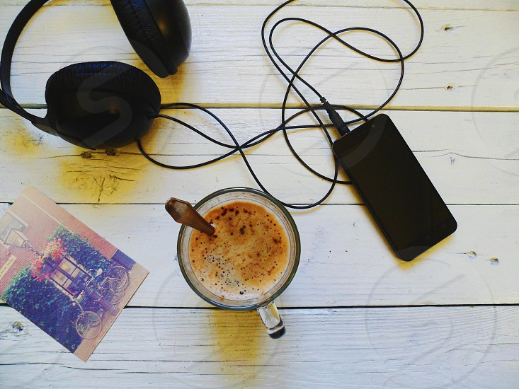 clear glass mug filled with beverage next to turned off black phone with headphones on brown wooden table photo