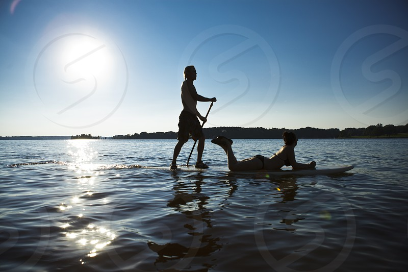 A man gives his lady a ride on a paddle board on a sunny day photo