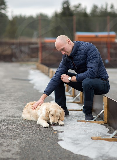 golden retriever and young man sitting outdoors photo