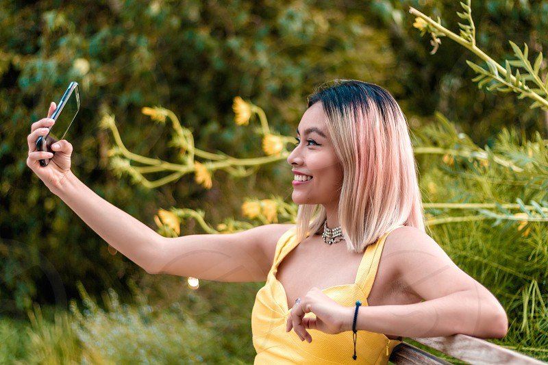 woman wearing yellow tank sweetheart top sitting on bench with plants behind hear taking a selfie photo photo
