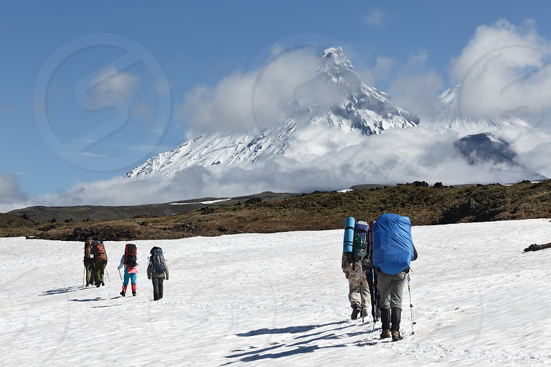 Hiking on Kamchatka: hiker goes in the mountain on the background of picturesque Klyuchevskaya group of volcanoes: Kamen Volcano active Klyuchevskoy Volcano and active Bezymianny Volcano on a sunny day. Russian Far East Kamchatka. photo