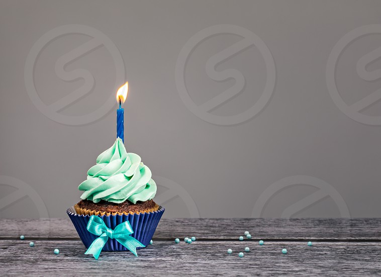 Blue Cupcake with bow sprinkles and one candle over a gray background. photo