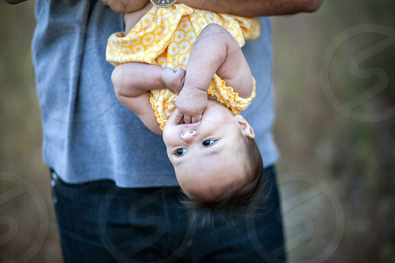 A baby is held upside down by dad. Blue jeans grey shirt yellow flower dress fingers trust calm mouth weeds outdoors photo