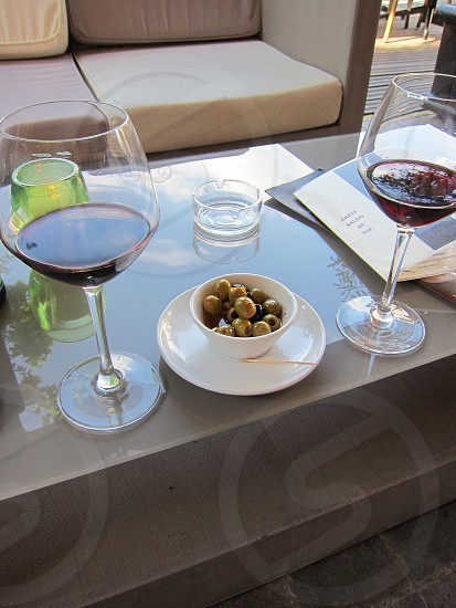 A bowl of olives and two glasses of wine on a bistro patio in France. photo