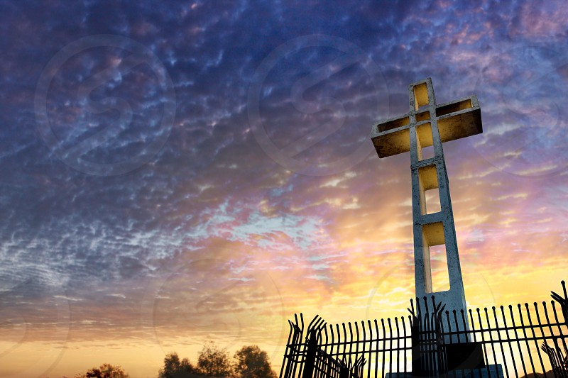 Looking up at a giant cross as the easter sun rises behind it in purple blue yellow and orange sky. photo
