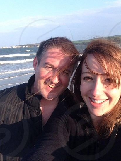 man and woman in black cloth smiling photo