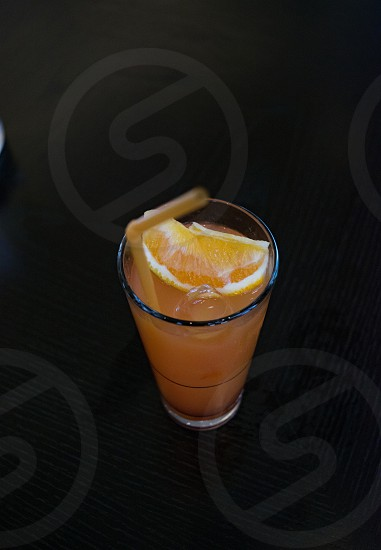 Close up high angle shot of fresh orange pina colada cocktail in glass on the dark surface and plastic straw photo