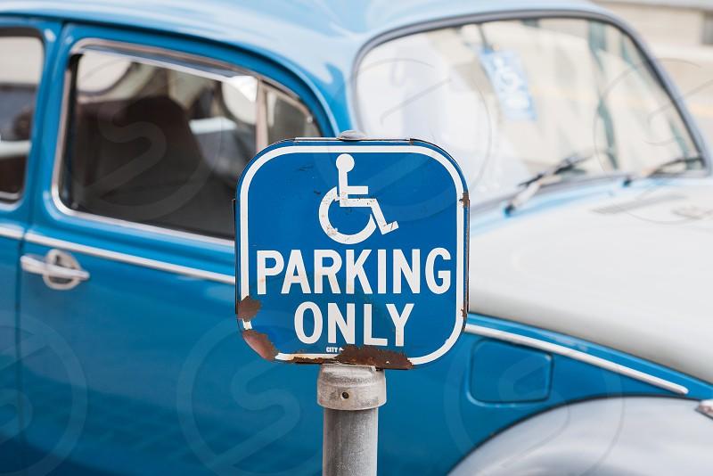 handicapped parking car blue bug signage sign law rule photo