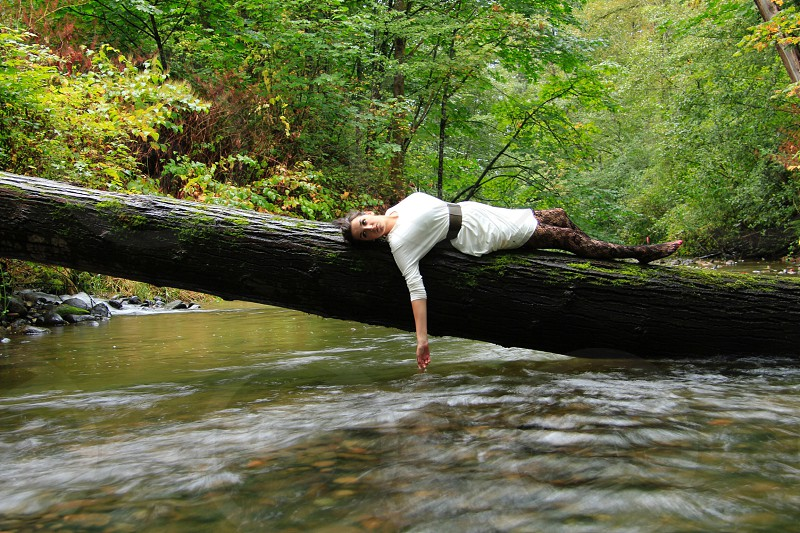 woman wearing white dress with black belt lying on tree trunk over body of water during daytime photo