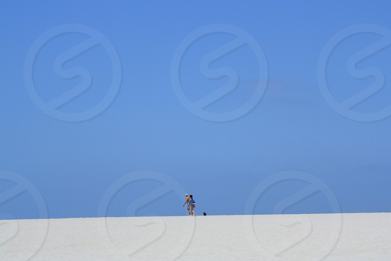 In the distance two people and a dog walk on a white sand beach near the horizon under a blue sky. photo