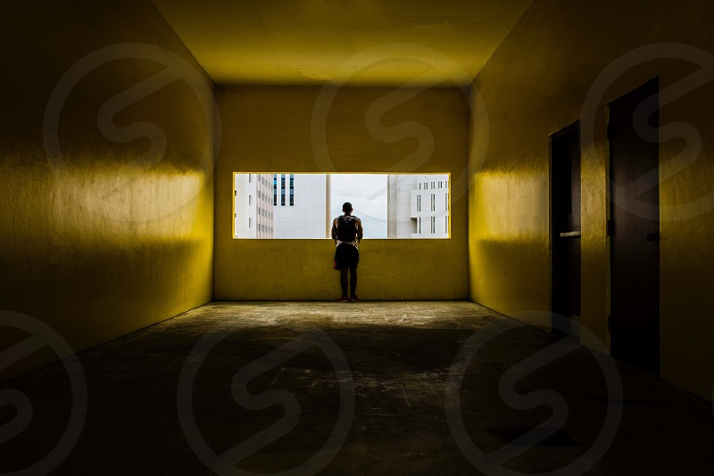 person standing in front of a building window photo