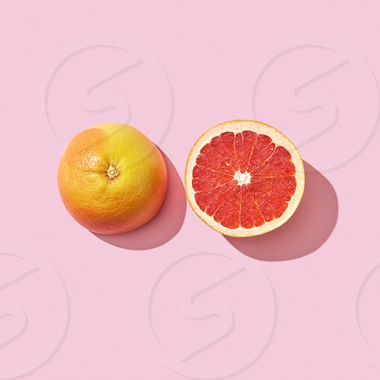 Halves juicy grapefruit presented on a pink background with reflection of shadow and copy space. Dietetic food. Top view photo