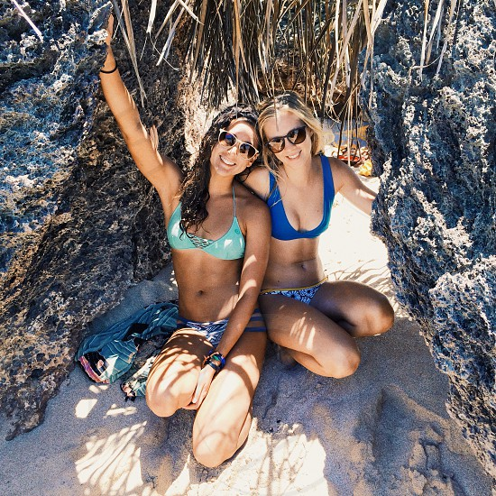 woman in blue bikini top smiling beside woman in white framed black lens wayfarer sunglasses photo