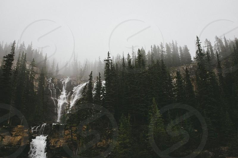 crashing waterfall on a pine tree mountainside under a hazy sky photo