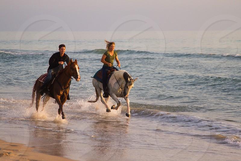Man and Woman riding horseback at the beach photo