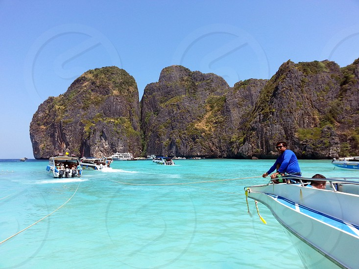 man in blue rashguard standing on white tip of boat near green covered rock formation in ocean water bed during daytime photo