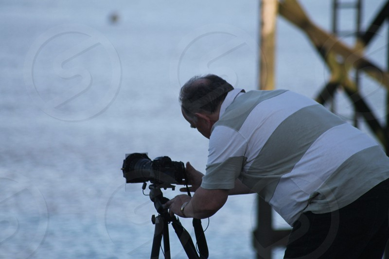 'Waiting for the moment ' photographer adjusting camera/tripod photo