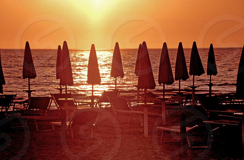 Sunset on the beach umbrellas Tuscany photo