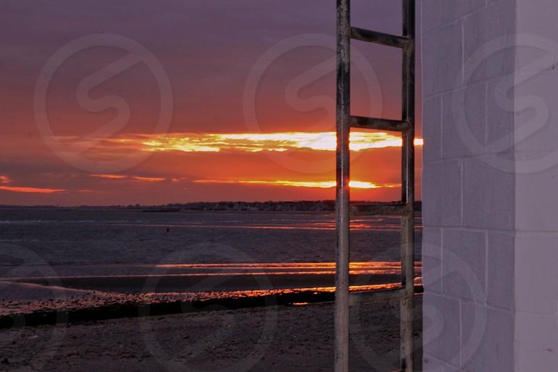 grey metal ladder near white brick wall near seashore at sunset photo