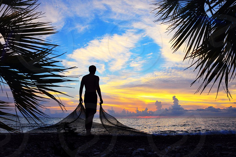 man standing holding fishnet facing sea photo
