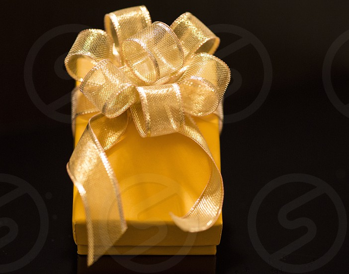 Golden bow yellow box black background  photo