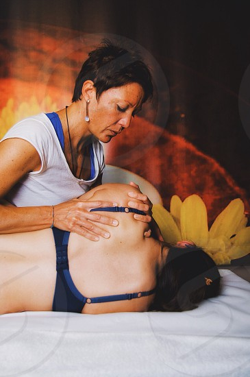 woman in white scoop neck cap sleeve shirt massaging another woman in blue brassiere lying on bed photo