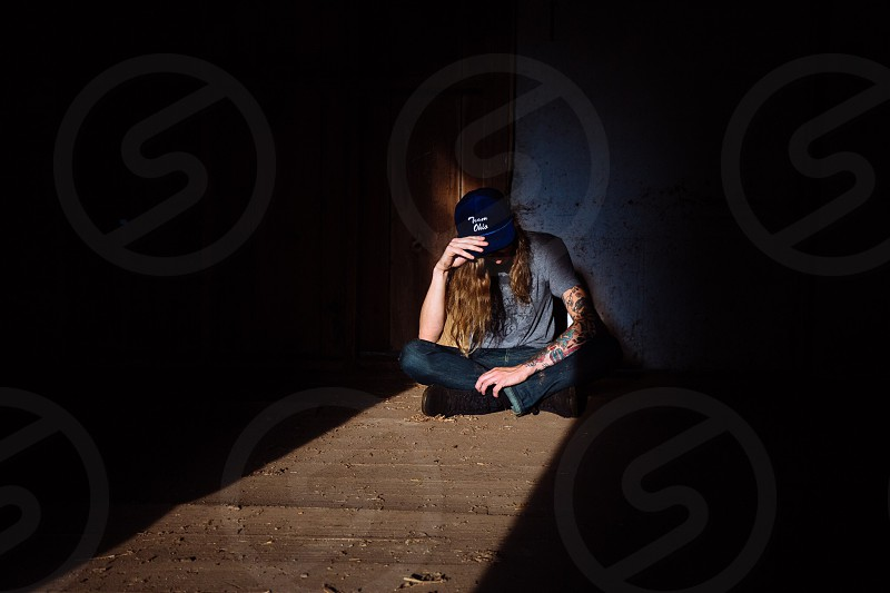 man with long hair in blue shirt and denim jeans sitting on the floor in the room photo