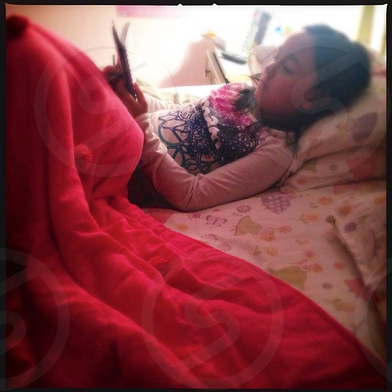 Little girl reading in bed photo