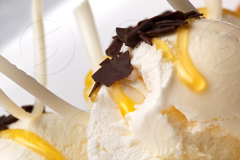 Vanilla ice cream drizzled with honey and topped with dark chocolate flakes close up view photo