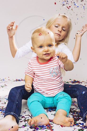 smiling blonde baby with blue eyes wearing a red striped shirt and blue cotton pants sitting in front of a blonde girl in a white top and blue jeans throwing confetti photo