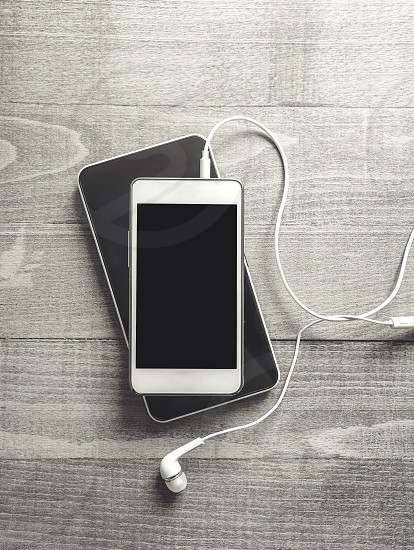 Black and white photo of smartphone with earphone  photo