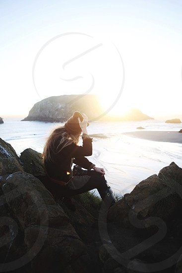 person wearing black jacket and beanie hat sitting on gray rocks near body of water photo