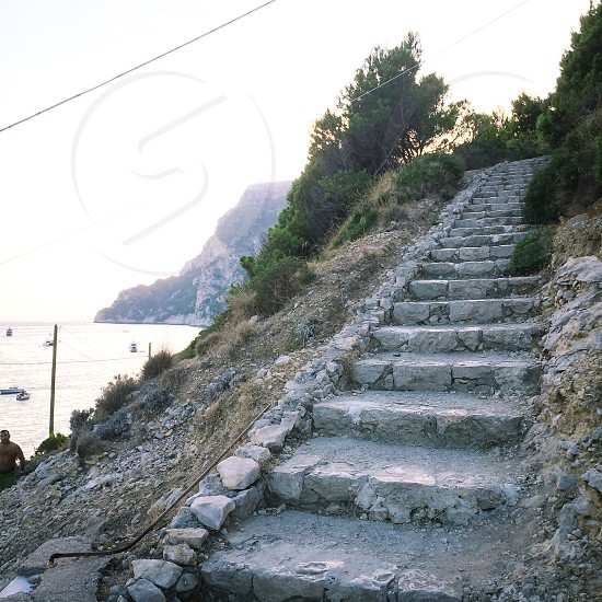 gray concrete stairs near body of water photo