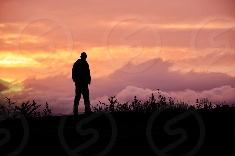 man standing on hill at sunrise with cloudy sky photo