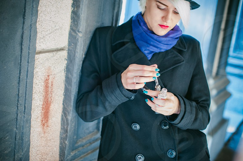 portrait of young beautiful woman with white hair in a black coat a skirt and a black hat smoking an electronic cigarette runs vape juice electronic cigarette. He holds a mechanical mod with RDA. photo