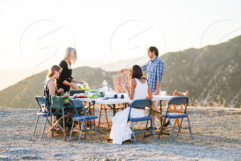 young adults picnicking in hills photo