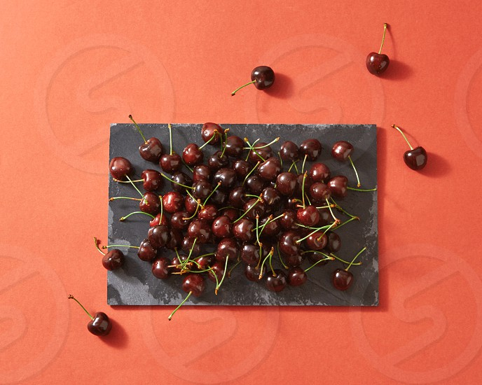 Summer berries background from red ripe cherries on dark stone board on a color background of the year 2019 Living Coral Pantone with place for text. Copy spase. photo