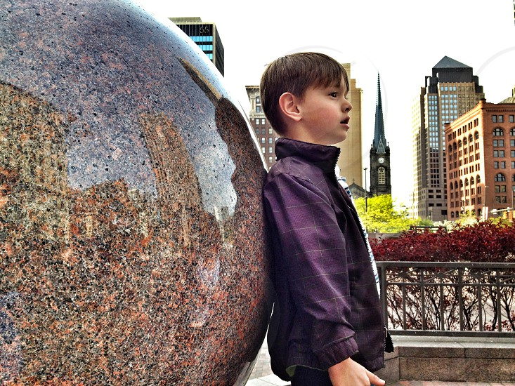 boy in dark purple jacket leaning against marble statue photo