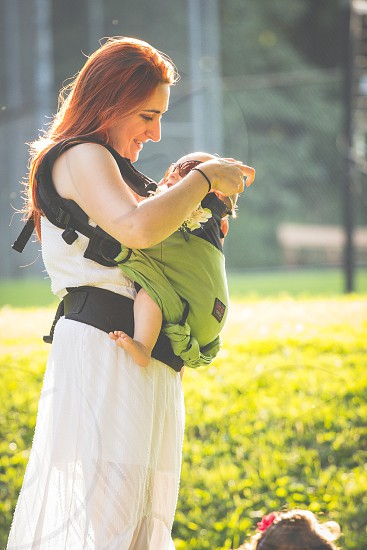 smiling woman wearing white sleeveless dress carrying baby using carrier during daytime photo