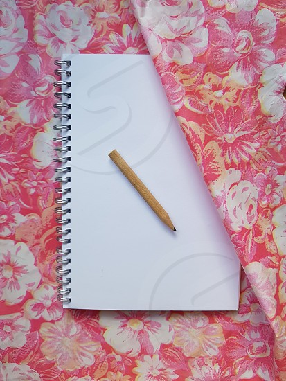 Notebook pen on pink background photo