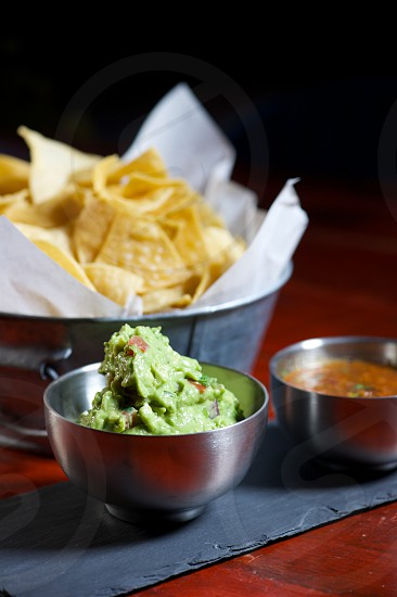 Chips and salsa with fresh guacamole in metal bowls on a rustic wood table photo
