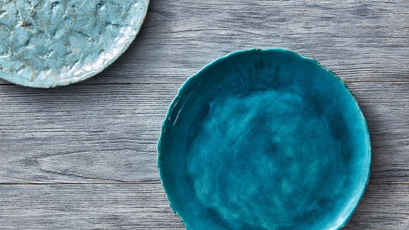 Clay handcraft empty blue plates covered with glazed  place under text on a gray wooden background. Flat lay photo