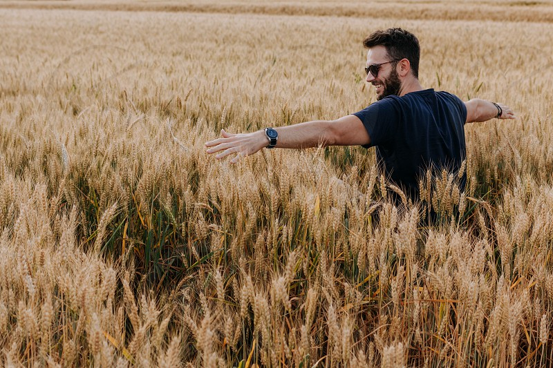 Young man in the wheat field with spread arms photo