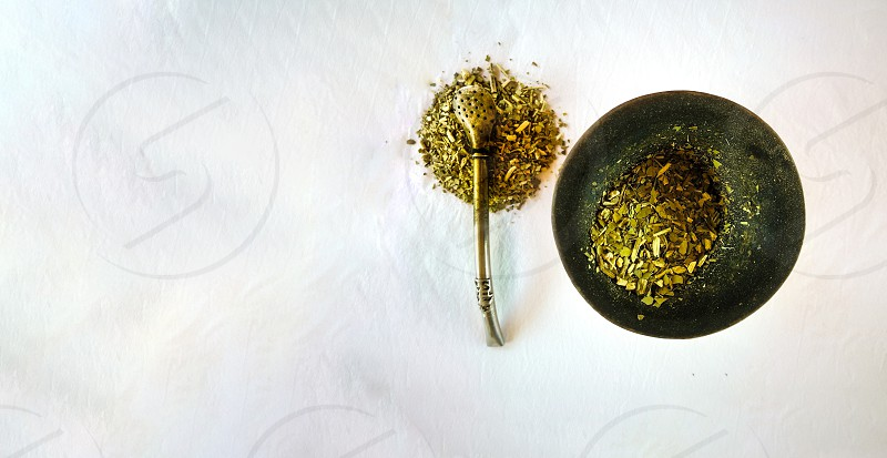 A cenital view of the yerba mate infusion with a withe background. A wooden gourd and the metal straw. photo