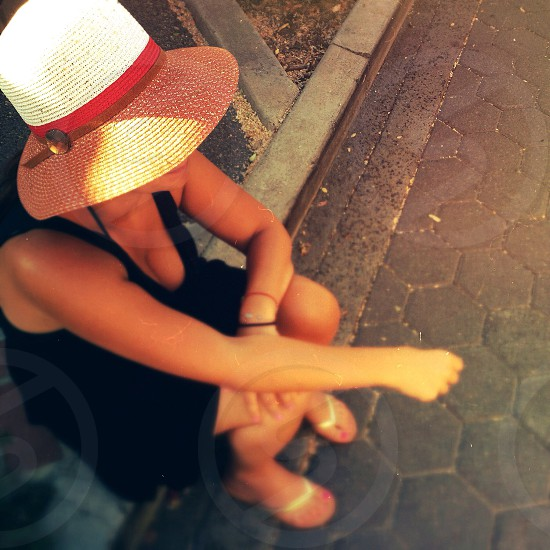 woman wearing sleeveless dress straw hat and flip flops sitting on concrete ground photo