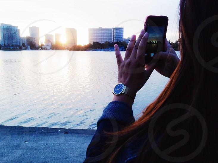 woman holding smartphone capturing photo