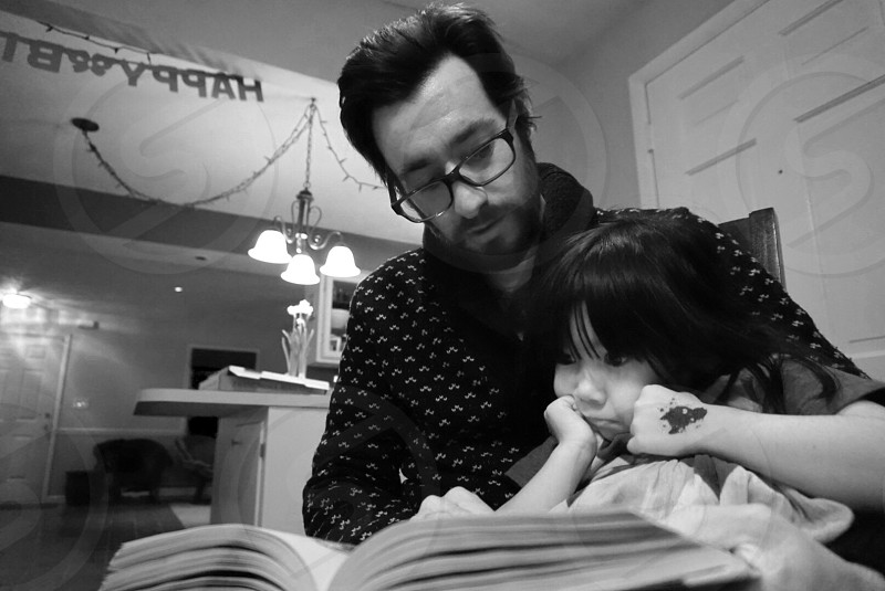 man teaching the girl how to read photo