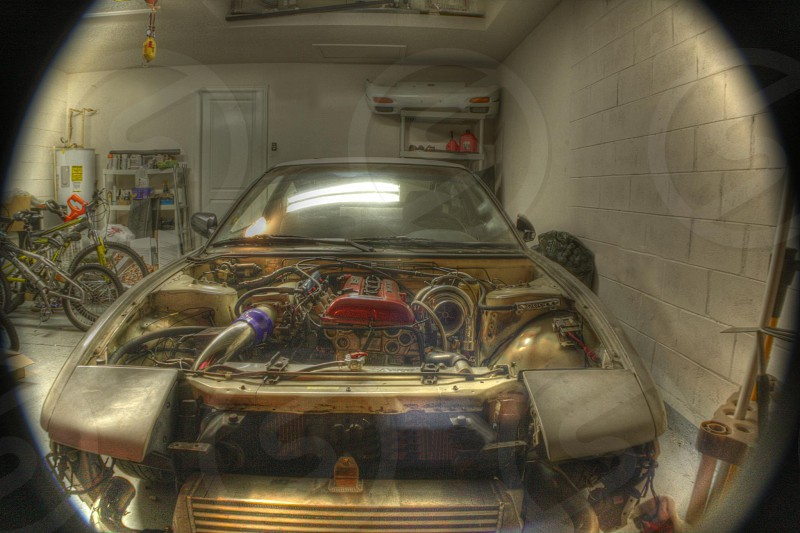 picture of car with hood missing in a garage photo