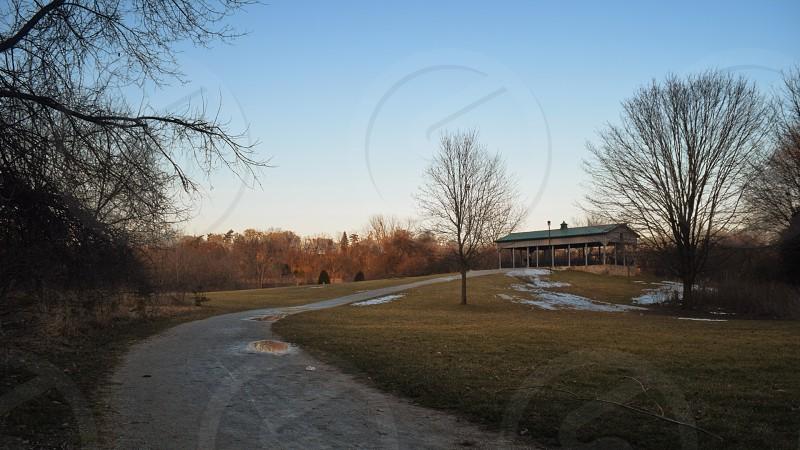 A park gazebo propped up on a hill at sunset photo