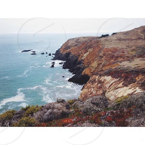 mountain side beside seashore photo